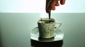 Rör med en sked, kaffe i en kopp arkivfilmer