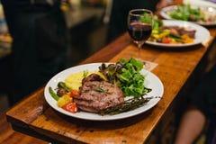 Rör stekt grisköttbiff som tjänas som med grönsaksidomaträtten, sallad och, mosa potatistoppning med den balsamic dressingen fotografering för bildbyråer