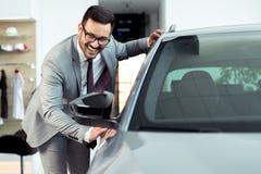 Rörande bil för lycklig man i auto show eller salong arkivfoto