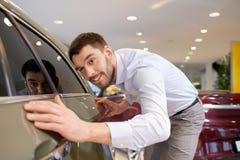 Rörande bil för lycklig man i auto show eller salong Fotografering för Bildbyråer