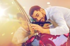 Rörande bil för lycklig man i auto show eller salong Royaltyfri Fotografi