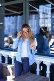 Rörande exponeringsglas för nätt flicka och hållasmartphone på kafét Royaltyfri Fotografi