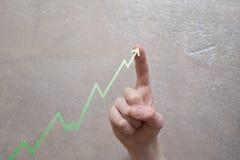 Rörande grön grafpil för finger royaltyfria bilder