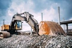 Rörande grus för industriell tung grävskopa på huvudvägkonstruktionsplats Åtskilligt industriellt maskineri på konstruktionsplats royaltyfria foton