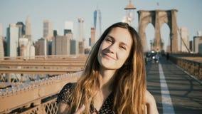 Rörande hår för ung europeisk härlig handelsresandeflicka som ser kameran och ler på den Brooklyn bron, New York City 4K arkivfilmer