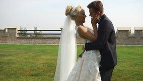 Rörande kamera in mot förälskat krama för unga attraktiva nygift personpar ömt i den härliga trädgården arkivfilmer