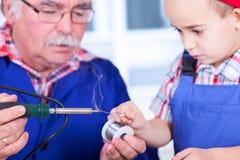 Rörande lödmetalltråd för barnbarn till den varma lödkolvspetsen Arkivbild