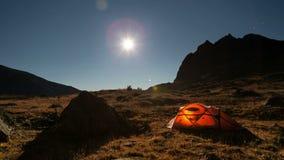 Rörande måne ovanför tältet på nattetidschackningsperioden stock video