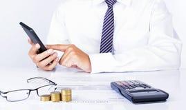 Rörande mobiltelefon för affärsman på kontorsskrivbordet för finanssymboler Arkivbild