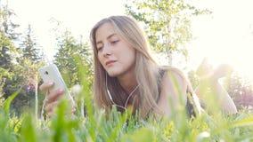 Rörande mobiltelefon för ung kvinna och ligga på äng arkivfilmer