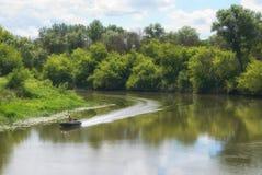 Rörande på ett motoriskt fartyg på en flod med forested kuster arkivfoton