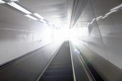Rörande rulltrappa i modern byggnad och ljus på bakgrund Royaltyfri Fotografi