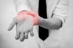 Rörande smärtsam handled för kontorsman (fokusen på handleden) royaltyfri fotografi