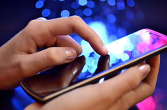 Rörande smart telefon för hand på blå bakgrund Arkivfoton