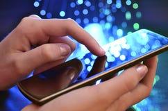 Rörande smart telefon för hand på blå bakgrund Royaltyfri Fotografi
