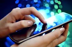 Rörande smart telefon för hand på grön bakgrund Fotografering för Bildbyråer
