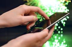 Rörande smart telefon för hand på grön bakgrund Royaltyfri Fotografi