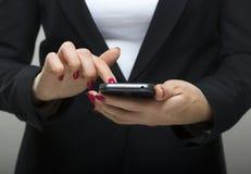 Rörande smartphone för affärskvinna i henne händer Royaltyfri Fotografi