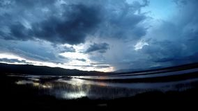 Rörande tidschackningsperiod för moln över sjösikt på solnedgången med regn- och stormbakgrund i bygd stock video