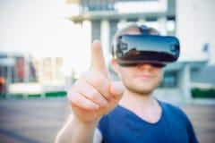 Rörande utrymme för ung man framme av honom i anseende för virtuell verklighetexponeringsglashörlurar med mikrofon mot modern byg Royaltyfria Bilder