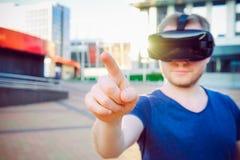 Rörande utrymme för ung man framme av honom i anseende för virtuell verklighetexponeringsglashörlurar med mikrofon mot modern byg Arkivbilder