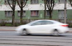 Rörande vit bil med effekt för rörelsesuddighet Arkivfoton