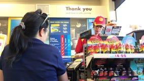 Rörelse av den köpande lottsedeln för kvinnan på checkout räknaren inom lämpligt lager för skalbensinstation arkivfilmer