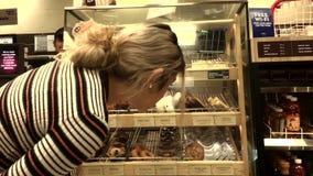 Rörelse av den kundköpandemat och arbetaren som lagerför donuts på skärmhylla stock video