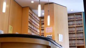 Rörelse av det tomma tand- kontoret med fulla mappar inom bokhyllan