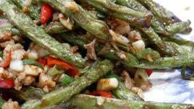 Rörelse av folk som äter den stekt haricot vert och varm peppar på tabellen inom kinesisk restaurang stock video
