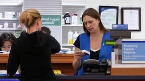 Rörelse av folk som betalar medicin på apotekavsnittet arkivfilmer