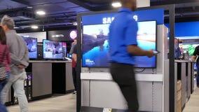 Rörelse av folk som söker efter en ny tv inom elektroniskt lager arkivfilmer