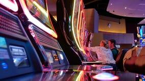 Rörelse av folk som spelar enarmade banditen inom kasino stock video