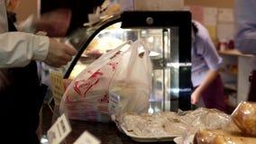 Rörelse av köpande bröd för folk och betalakassa stock video