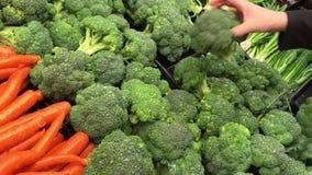 Rörelse av räddningen för insida för kvinnaköpandebroccoli på Foodslager lager videofilmer