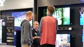 Rörelse av shopparen som ser ny TV för att köpa arkivfilmer