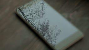 Rörelse av träden reflekteras i skärmen av din smartphone stock video