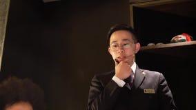 Rörelse av uppassaren som tar beställning för kund inom den Shang Palace restaurangen arkivfilmer