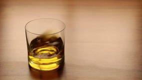 R?relse av whisky i ett exponeringsglasanseende p? tabellen stock video