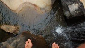 Rörelse för Closeupmanfot över lilla Rocky River lager videofilmer