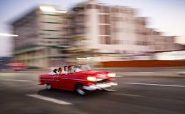 Rörelse-suddig ` 1950 s Chevy kör förgångna höga löneförhöjningar i havannacigarren, Cu Arkivbilder