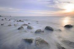 Rörelse vinkar på stenar på stranden Arkivfoto
