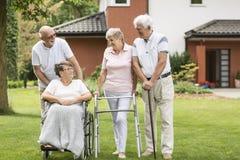 Rörelsehindrad äldre kvinna i en rullstol och lyckliga vänner i royaltyfri bild