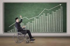 Rörelsehindrad affärsman med det finansiella diagrammet på den svart tavlan Arkivfoton