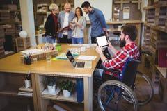Rörelsehindrad affärsman som använder den digitala minnestavlan på skrivbordet arkivbild
