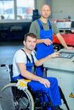 Rörelsehindrad arbetare i rullstol i fabrik och kollega royaltyfria foton
