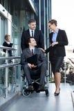 Rörelsehindrad arbetare och hans medarbetare Arkivbild