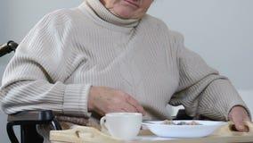 Rörelsehindrad dam för pensionär som vägrar att äta matställen i sjukhuset, sjuksköterska som bort tar mat lager videofilmer