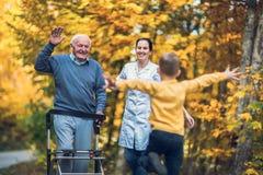 Rörelsehindrad farfar i fotgängaren som välkomnar hans lyckliga gran fotografering för bildbyråer