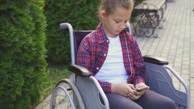Rörelsehindrad flicka i en rullstol genom att använda telefonen Arkivbild